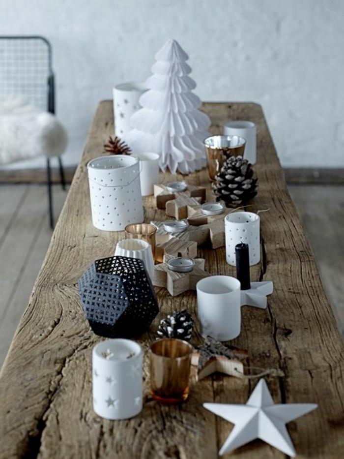 table scandinave en bois brut, sapin en papier blanc, porte bougies géométriques en forme d'étoiles, pommes de pin