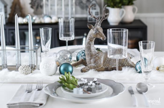 deco salle a manger, assiettes blanches, table blanche, verres à vin, verres à champagne, cerf décoratif, boules de Noel