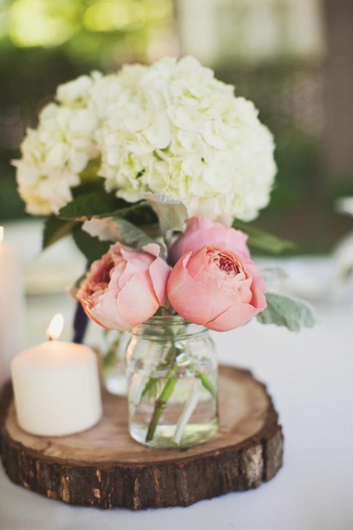 rondin de bois avec deux vases et une bougie allumée, décoration table romantique avec roses et hortensias