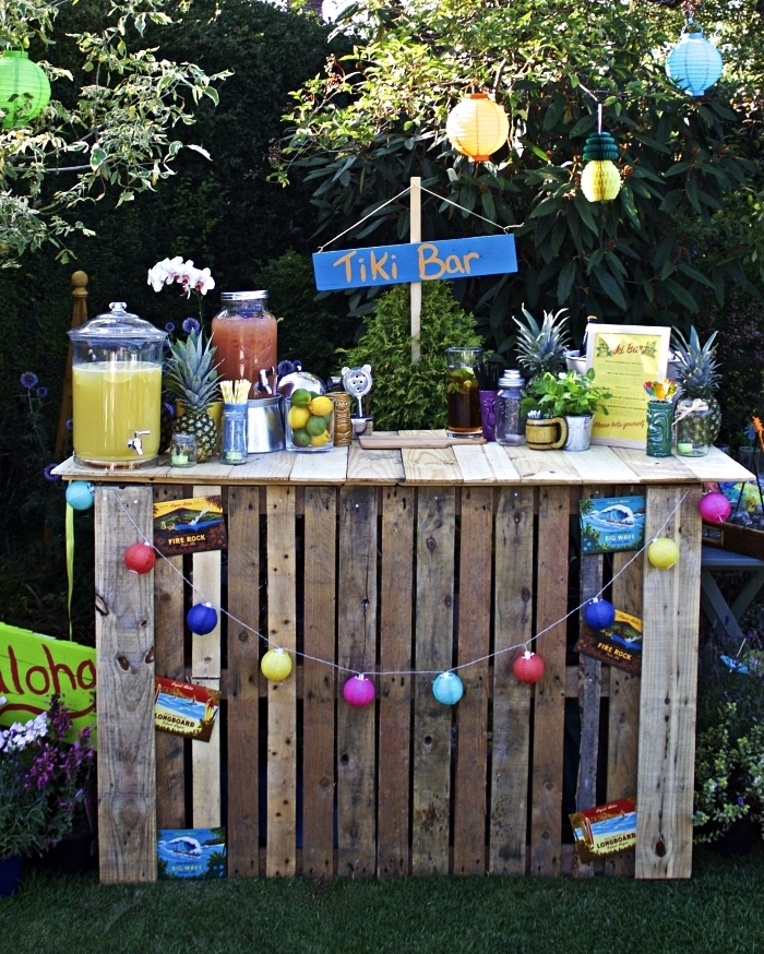 deco bar guinguette avec bonbonnières à jus, ananas, guirlande colorée et lanternes en papier, fabriquer un tiki bar dans son jardin