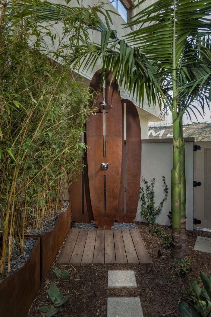 ambiance exotique dans une cour arrière avec petite douche fixe en bois, choix de plantes pour salle de bain jardin