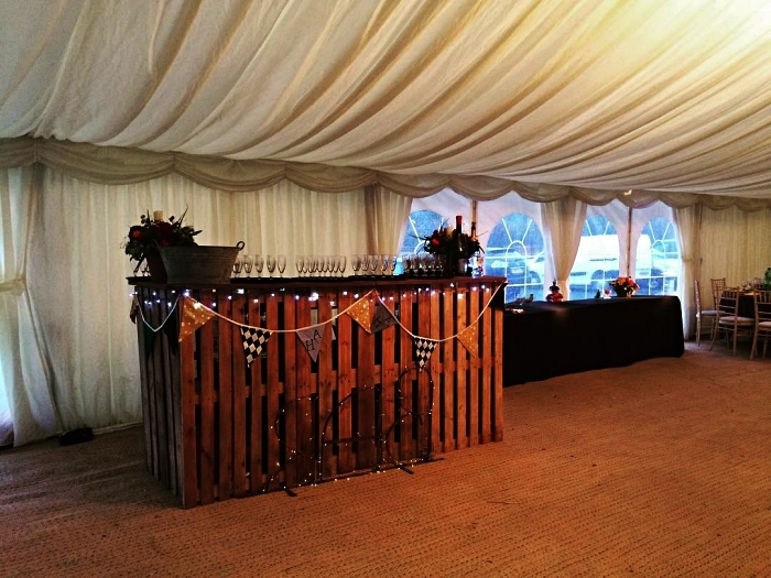 salle de réception mariage avec coin bar en bois récup décoré d'une guirlande à fanions, fabriquer un bar à boissons avec des palettes