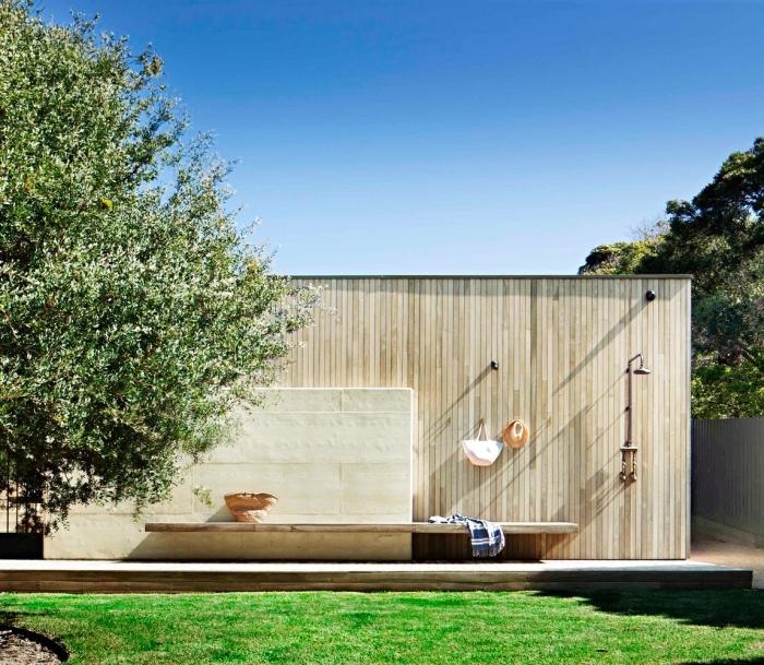 amenagement jardin paysager, modèle de salle d'eau extérieure avec douche en métal et crochets fixés sur murs pour serviettes