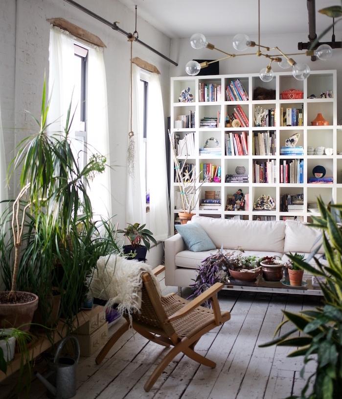 deco exotique salon avec canapé blanc, table basse bois avec pots de fleurs rangés dessus, plusieurs plantes en pots, murs blanc, suspension originale à plusieurs ampoules