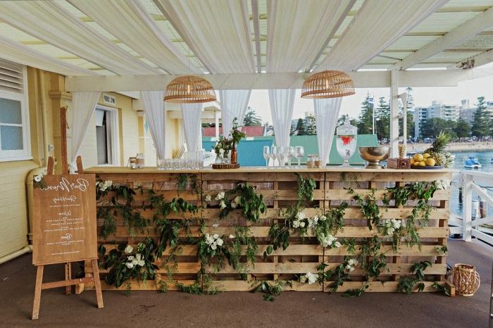 décoration de mariage à faire soi même, deco bar à champagne en palettes avec fleurs et branches vertes