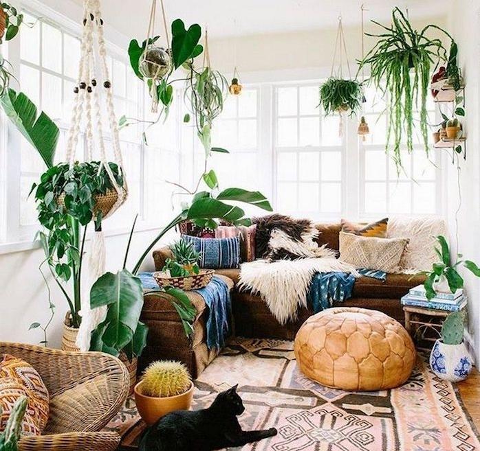 deo boheme chic dans le salon, pouf beige, tapis oriental, chaise de rotin, canapé d angle marron, coussins orientaux, murs blancs et plantes vertes suspendues