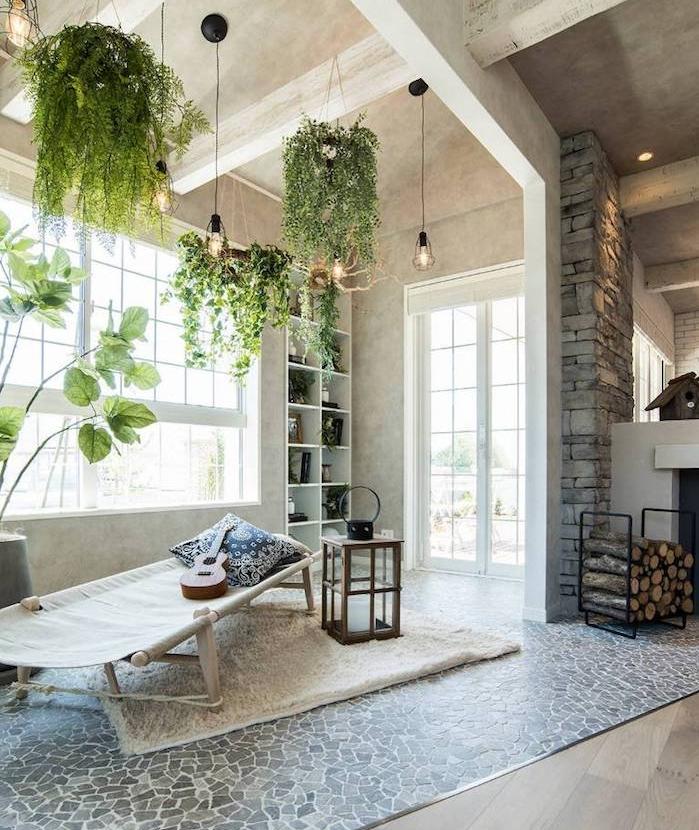 deco salon aux poutres apparentes blanches, cheminée bois, carrelage mosaique de pierre, lit boheme, pots de fleurs suspendus, ampoules romantiques