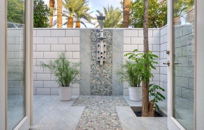 modèle de salle de bain pinterest dans le jardin aux murs en carreaux blancs avec une douche pluie en inox et pan de mur en pierre