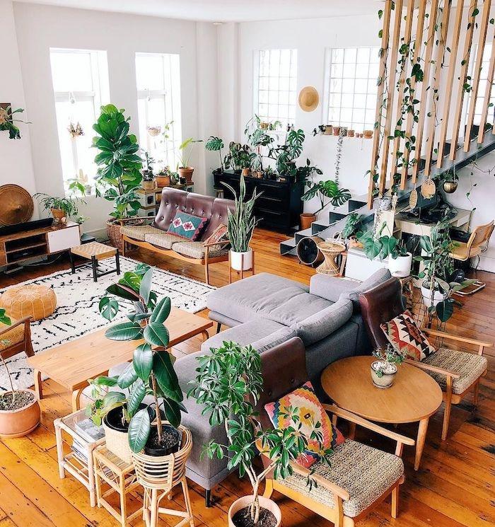 deco salon esprit urban jungle avec végétation abondante, canapé gris, mobilier et parquet bois et murs blancs, montée escalier treillis