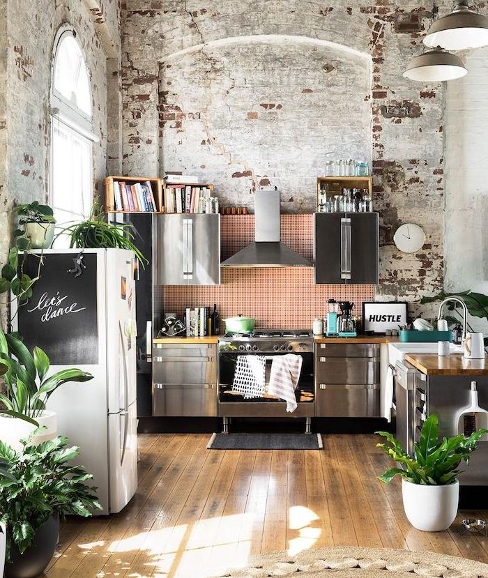 idee deco cuisine industrielle à murs de briques, facade cuisine inox, frigo blanc à tableau noir, parquet bois brut et motif jungle introduit avec végétaux