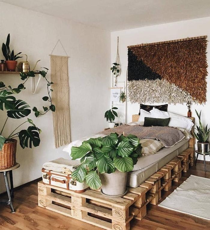 deco chambre boheme chic avec lit en palette a faire soi meme, matelas gris, bout de lit de plante en pot et malle vintage, monstera deliciosa sur table de service, macramé et tissage mural