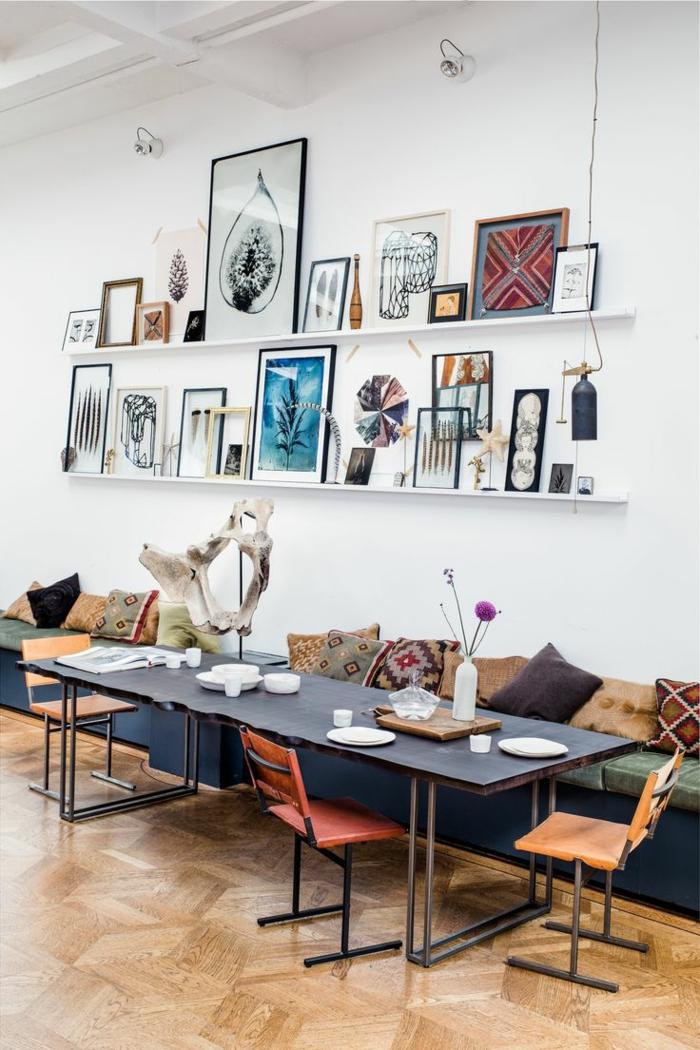 tablettes murales blanches, longue table en bois, chaises minimalistes, plusieurs tableaux encadrés