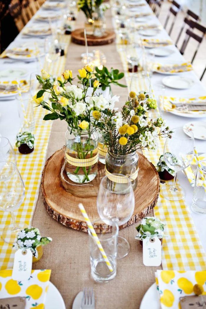 chemin de table carreaux jaunes et blancs, rondins de bois, vases en verre, bouquets de fleurs des champs