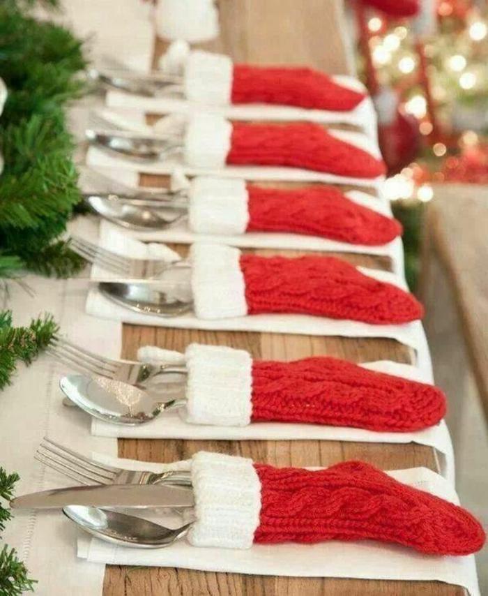 chemin de table de noel avec branches de pin, chaussettes père Noel pour y poser les ustensiles, table en bois