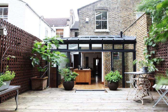 extension pour abriter une cuisine avec ilot central bois ouverte sur terrasse de bois avec végétaux et petit salon de jardin