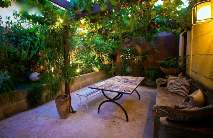 amenagement petit jardin, grande banquette en bois, pot de fleurs avec arbres plantés, petit espace extérieur cosy