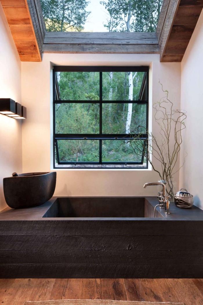 idée deco salle de bain zen avec plancher en bois et murs blancs aménagée avec baignoire et lavabo en noir