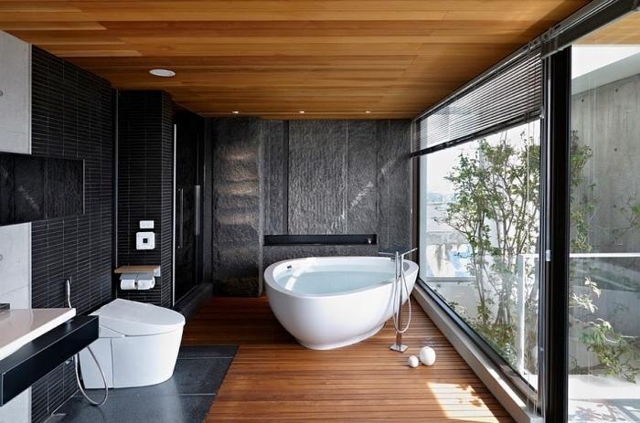 comment décorer une salle de bain zen avec carrelage mural en noir, salle de bain avec plafond et plancher en bois aux murs noirs