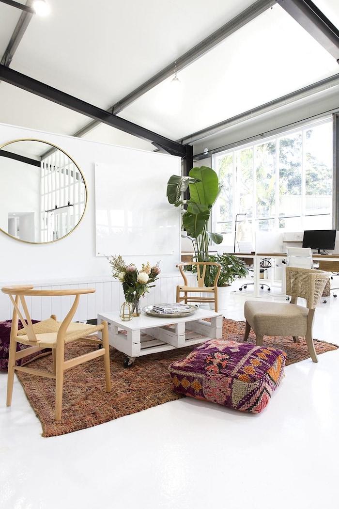 Salon bien aménagé, tapis berbère, pouf sur le sol à motif ethnique, table basse de palettes, vase de fleurs, plante verte, miroir ronde grande