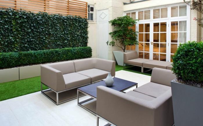 salon de jardin, canapés gris, table basse noire, verdure rampante, cloison lattes de bois, gazon tondu