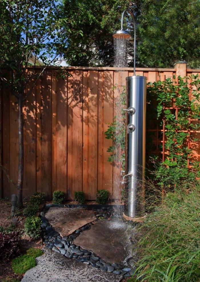 décoration cour arrière avec plantes vertes et allées en dalles, modèle de douche solaire en inox pour le jardin