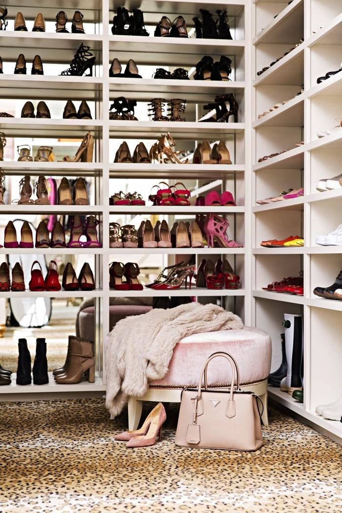 coin dressing à chaussures dans une pièce à part aménagé avec des meubles à étagères hauts avec un pouf en velours rose