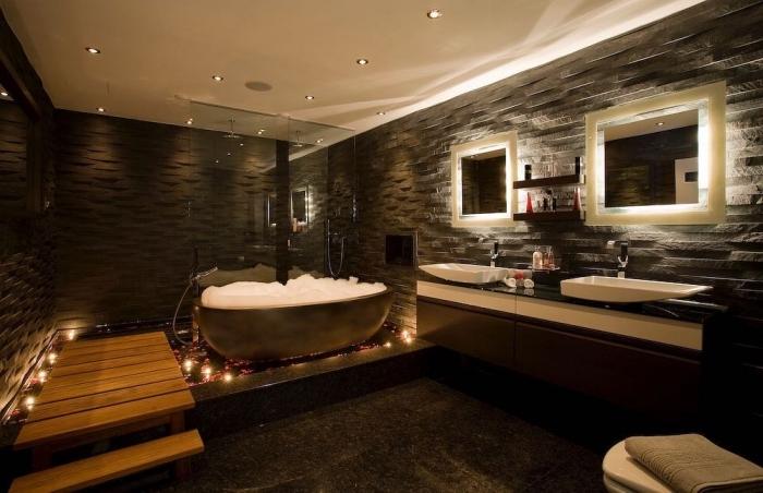 idée salle de bain zen aux murs en pierre foncé et plafond blanc avec marches en bois, agencement salle de bain baignoire et cabine de douche