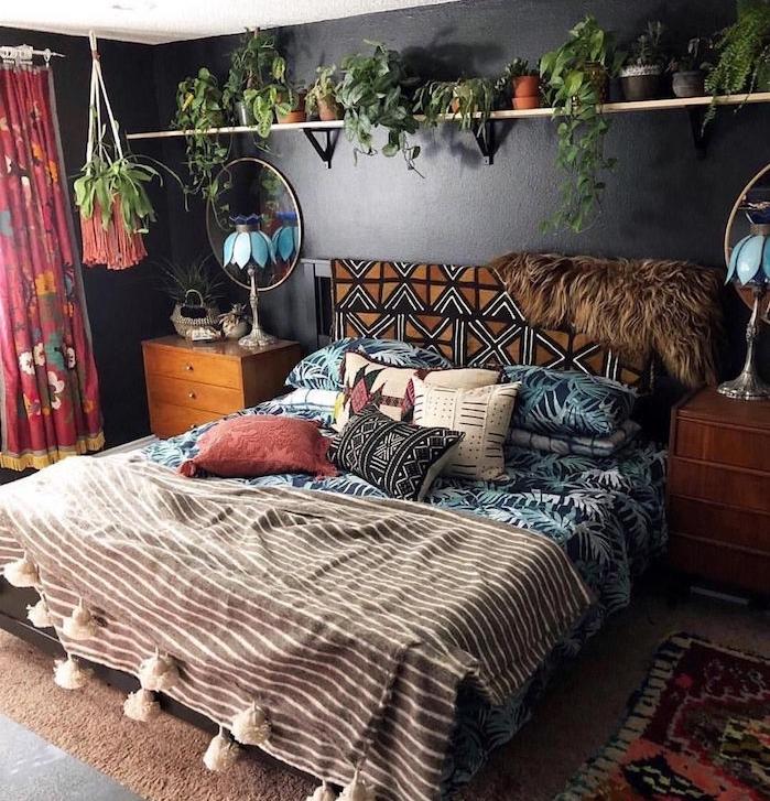 couleur mur noir, linge de lit tropical et hippie chic, tapis marron, étagère surchargée de petits pots de fleurs, commode bois vintage, miroir rond, rideaux colorés