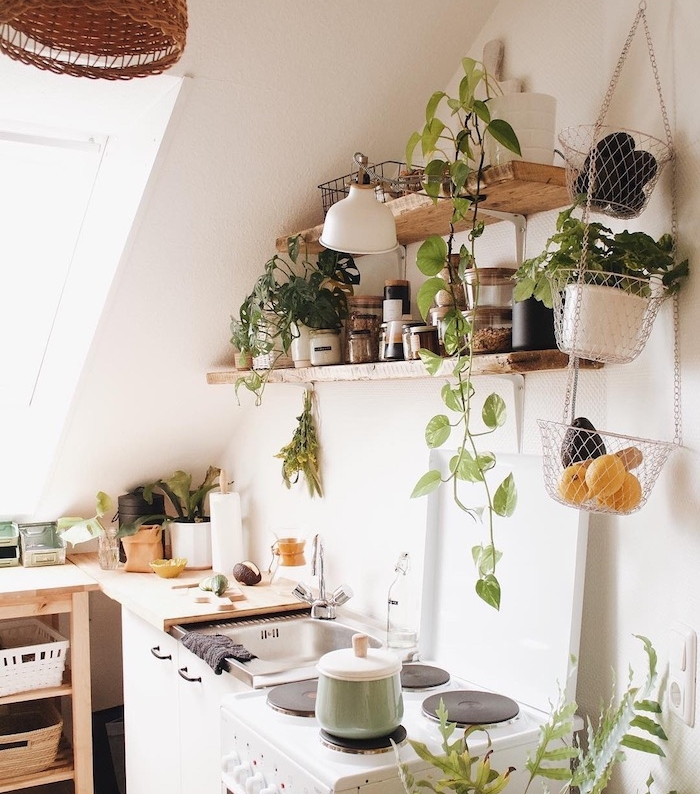 amenagement cuisine sous pente, étagères bois brut décorés de petits végétaux, herbes et ingredients, meuble cuisine bois, murs blancs, petites touches deco exotique