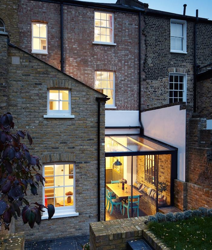 agrandir sa maison en exploitant l espace entre deux murs avec une salle à manger en table de bois et chaises bleues et banc de bois