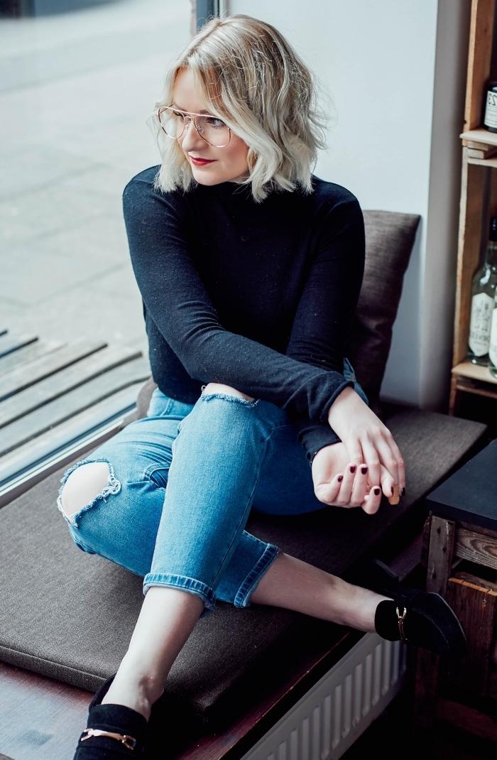 tenue femme en jeans et pull noir, maquillage avec rouge à lèvre rouge mate, modèle lunettes de vue femme à cadre or, coupe carré bouclé