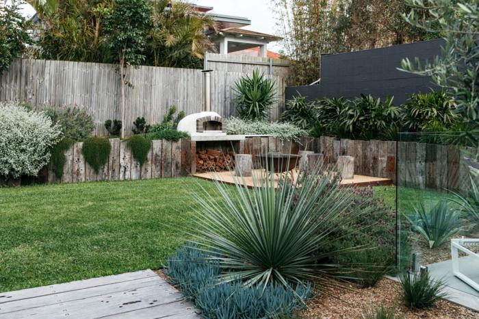 foyer avec range-bûches, petite terrasse en bois, pelouse tondue, arbustes, clôture en bois, parterre surélevé