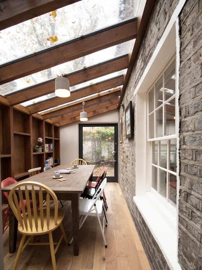 extension ossature bois et vitres pour abriter une salle à manger avec table à diner bois et chaises dépareillées sur parquet bois, mur de rangement