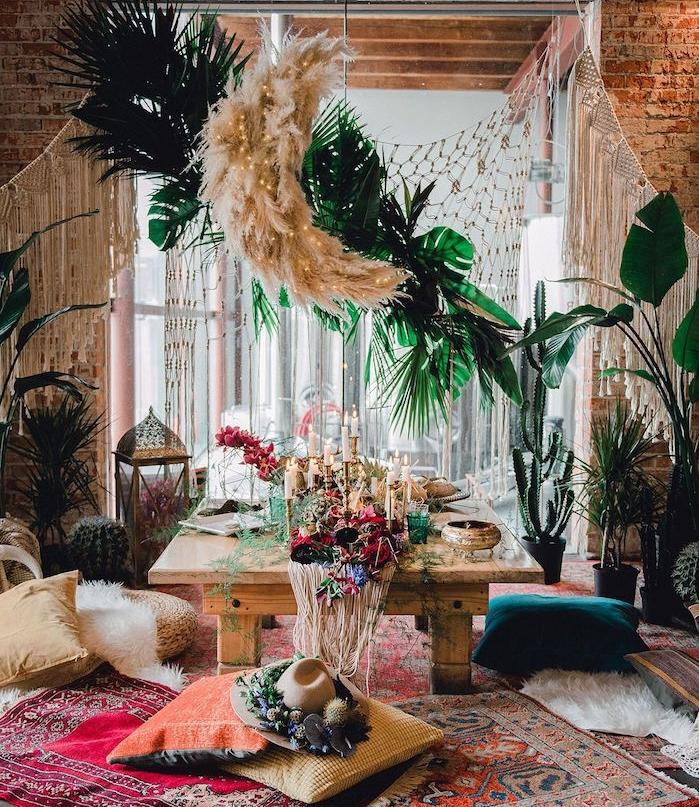 interieur deco boheme salon avec table basse bois brut, plusieurs coussins par sol et tapis esprit oriental, vegetation verte, mur de briques