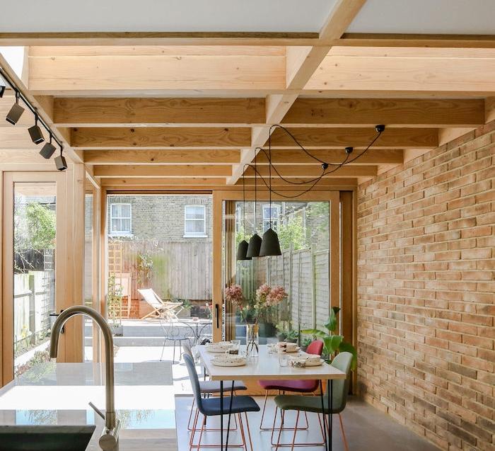 modele extension maison bois originale avec des poutres apparentes, suspensions industrielles, table à manger scandinave et chaises dépareillées, ilot central à coté, ouverture sur jardin