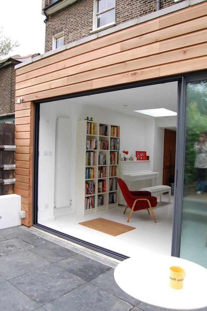 coin salon minimaliste avec bibliotheque scandinave blanche, chaise rouge et piano blanc accueillis par une extension en bois à vitraux