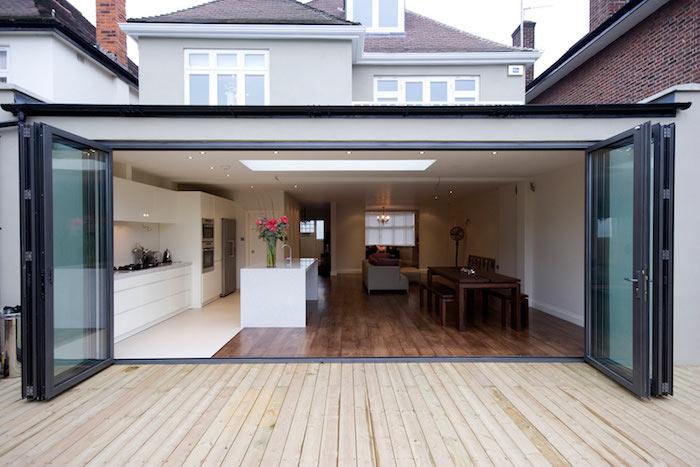 mini studio 20 m2 construit en extension avec cuisine blanche avec ilot central ouverte sur une salle à manger bois sur parquet bois foncé