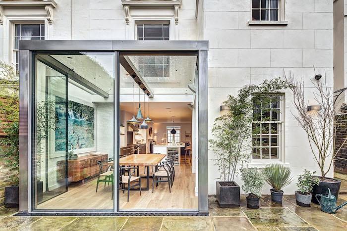 maison traditionnelle de pierre avec extension moderne industrielle pour salle à manger avec table et chaises bois et metal et vaisselier horizontal anciem