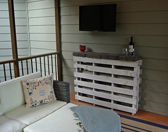 bar en palette avec rangement pour bouteilles installé à côté du salon de jardin en résine tressée sur la véranda