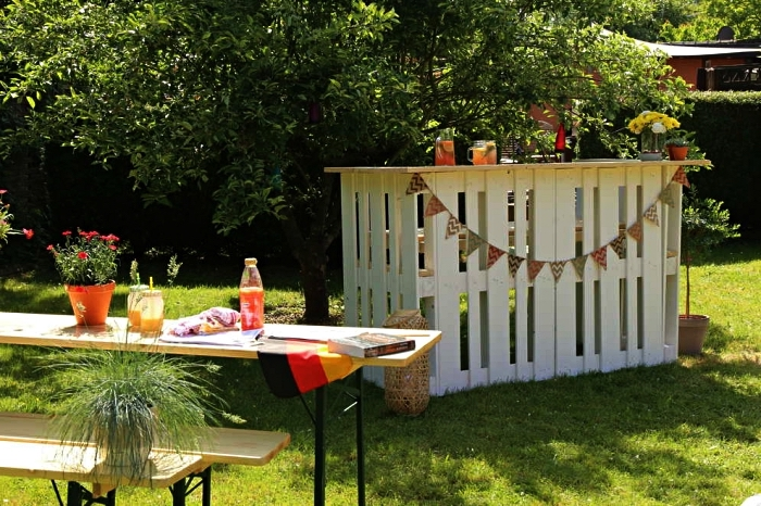 meuble palette bois pour le jardin ou la terrasse, bar de jardin en palettes décoré d'une guirlande à fanions installé à côté du salon de jardin