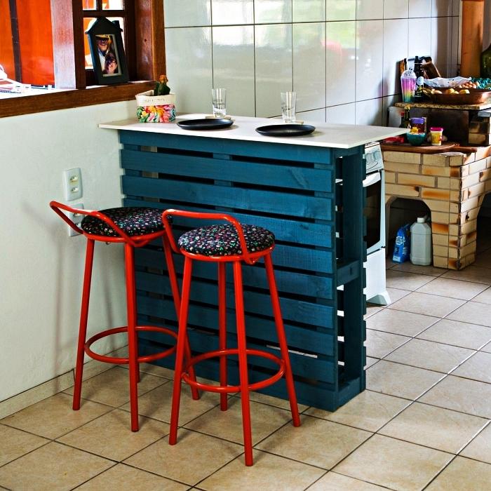 un bar de cuisine en palette récup repeinte en bleu canard, ilot cuisine palette recyclée avec deux tabourets de bar en métal rouge