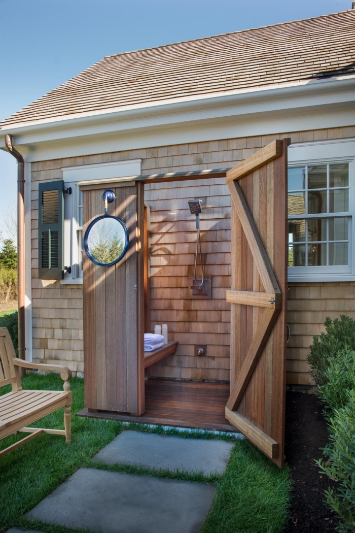 idée comment décorer une salle de bain en plein air avec portes en bois et douche fixe en métal, modèle de miroir rond