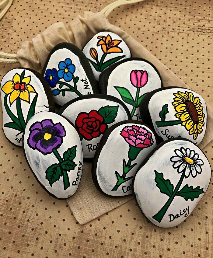 l'art de la peinture sur galet, peindre des fleurs sur des galets en noir et blanc, déco de jardin avec des galets à motifs fleurs