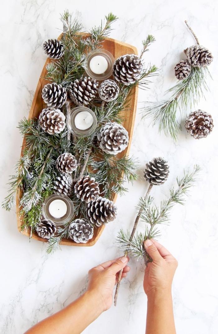 décoration avec pommes de pin, plateau en bois, branches de pin, décoration table scandinave
