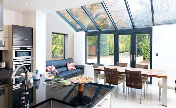 agrandissement maison contemporaine pour accueillir une salle à manger avec chaises et table à manger en bois et canapé cuir noir à coté, plan cuisine ouverte sur salle à manger