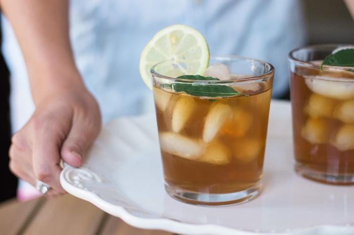 idée comment servir un thé glacé avec feuilles d'herbes vertes et tranches de citron, exemple boisson aux fruits et glaçons