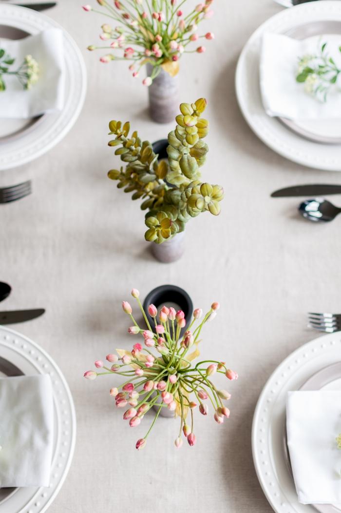 centre de table avec vases cylindriques au aspect béton, assiettes blanches, ustensiles sur la table de fête