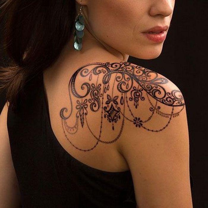 tatouage épaule femme, tatouage pendentifs, boucles d oreille perlées, motifs floraux, débardeur noir