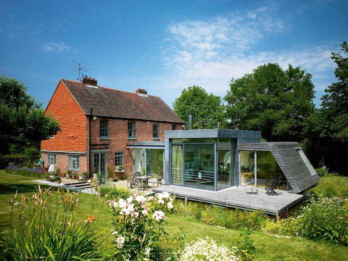 grande extension indépendante sur une terrasse en bois pour accueillir tout un studio à coté d une maison de campagne en briques