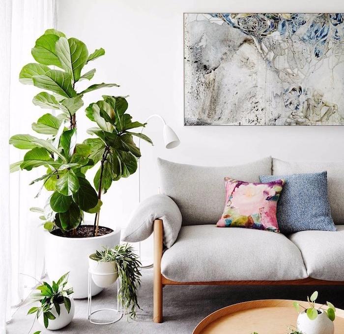 installer un grand pot de fleur dans un coin de la pièce, canapé bois avec coussin gris, deco murale cadre art abstrait, table basse ronde